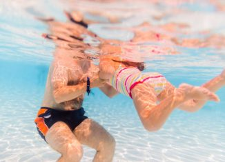 Jeune papa qui apprend à nager à sa fille dans une piscine