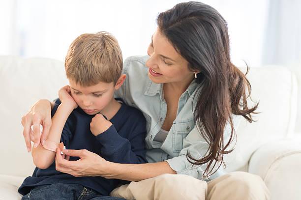 Maman qui met un pansement sur le bras de son fils qui s'est fait mal