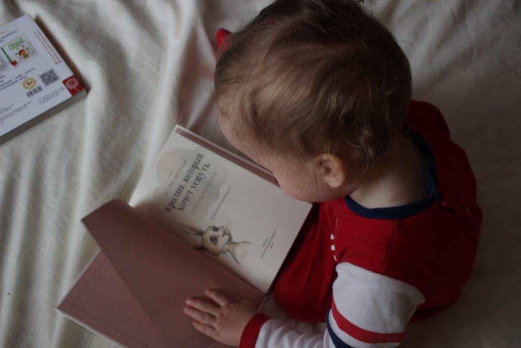 Un enfant qui lit un livre jeunesse
