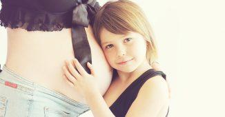 Une petite fille écoutant le bébé dans le ventre de sa maman