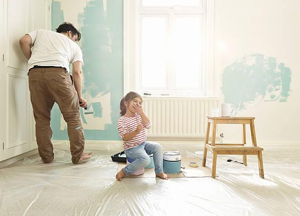 Jeune papa qui peint une chambre d'enfant avec sa fille
