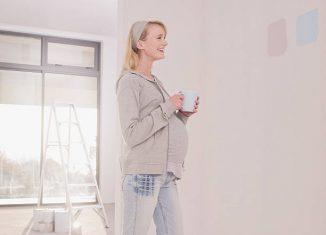Femme enceinte qui essaye de choisir la couleur de la peinture de la chambre de son bébé