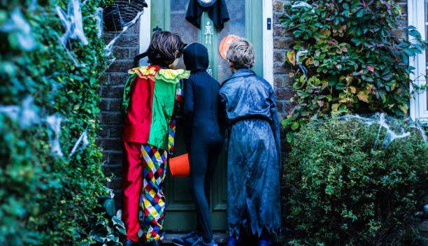 Trois enfants déguisés qui frappent à une porte à Halloween
