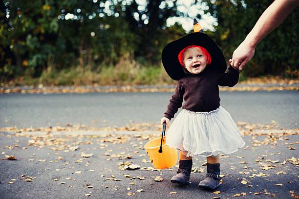 Petite fille déguisée en sorcière qui se promène dans la rue avec un panier orange