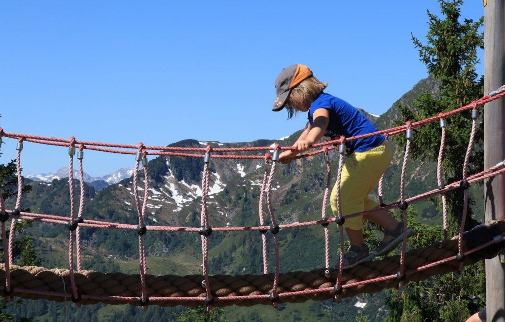 Enfant qui marche sur un pont suspendu à la montagne