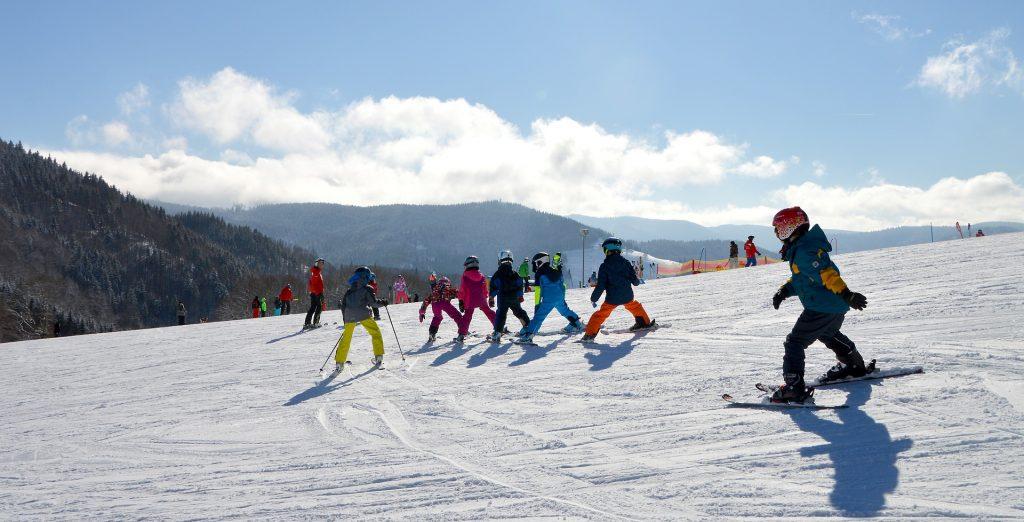Groupe d'enfants qui font du ski à la montagne sous un ciel bleu