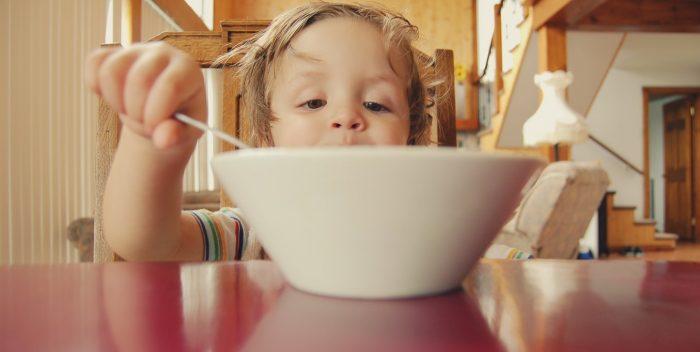 Enfant qui mange dans son assiette comme un grand