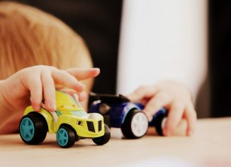Enfant qui joue avec des petites voitures pour s'éduquer sur la prévention routière